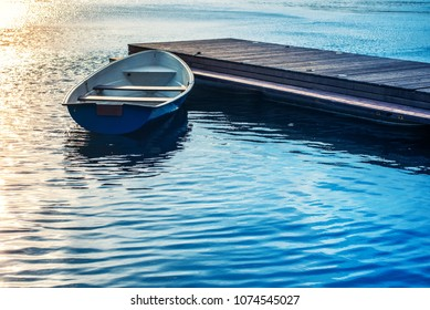 A boat tied to a wooden pier on the lake in the evening at sunset