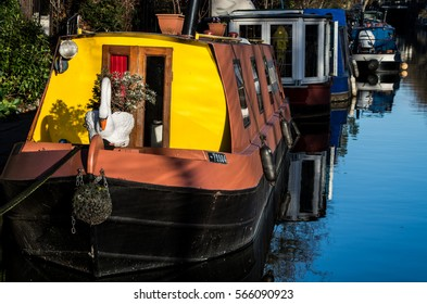 Boat, trees, birds are reflecting over Regent's Canal while people walks quietly along the river side.