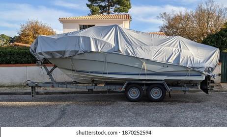 boat under tarpaulin tarp on car trailer