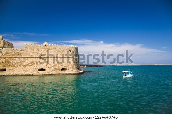 Boat under the walls of Koules Fortress in Heraklion. Fortress on the sea, tourist attraction of the city of Heraklion. Historic building in Crete, Greece.
