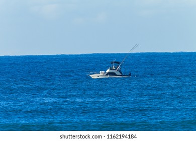 Boat vessel game fishing crew cruising trawling with rods high lines and lures out into blue ocean seas landscape.