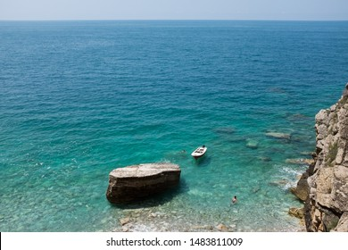 Boat in the water in a blue lagoon, with two unrecognizable swimmers, nudist beach or getaway location