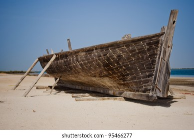 Boat from wood standing on sand