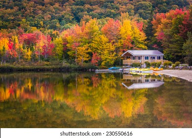 Boathouse and fall colors reflecting in Echo Lake, in Franconia Notch State Park, New Hampshire.