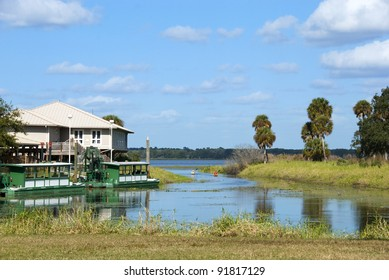 Boathouse on Upper Myakka Lake in Florida on a bright winter day.  There are 2 small people kayaking in the middle distance.