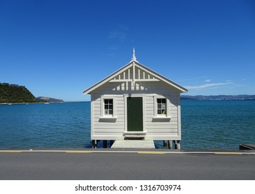 Boathouse at waters edge, Lowry Bay Wellington harbour New Zealand