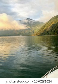 Boating In The Calm Sea Between Misty Mountains