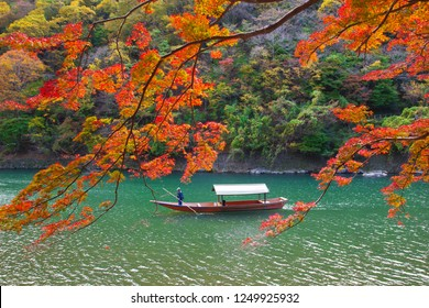 Boatman paddling the boat on the heritage river at Arashiyama in red maple autumns season along the river in Kyoto, Japan.