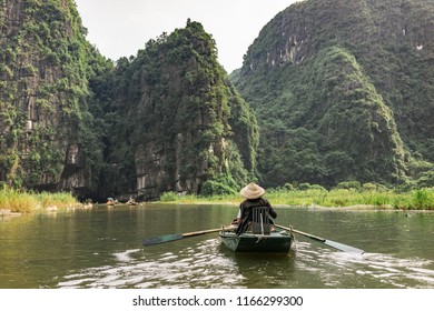 Boatride from Vung Tram Pier. Traditional paddle-boat trip lets the tourists truly appreciate the serenity and beauty of nature along the Ngo Dong River, the grottoes and limestone karsts of Tam Coc.