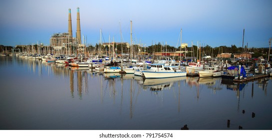 Boats afloat in marina on calm evening with pastel sky and reflections in shiny water and power plant smokestacks in background.