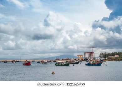 Boats anchored in Arousa Island fishing harbor under stormy cumulonimbus