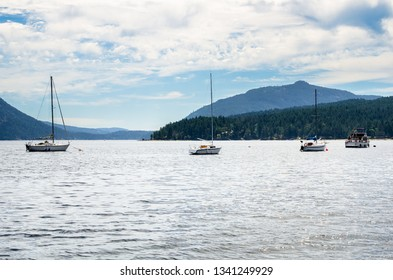 Boats Anchored in a Bay with Wooded Coastline and Cloudy Sky. Mapple Bay, BC, Canada.