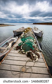 Boats anchored by a wooden pier covered in fishing nets with floaters near a fisherman village on the Romanian Black Sea coast under dramatic sky during summer