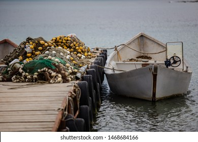 Boats anchored by a wooden pier covered in fishing nets with floaters near a fisherman village on the Romanian Black Sea coast during summer