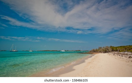 Boats anchored off a beautiful island in the Bahamas.