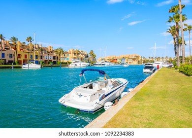 Boats anchoring in Sotogrande marina with colorful houses, Andalusia, Spain