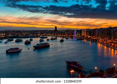 Boats in the bay and illuminated buildings along the shoreline during beautiful sunset in city of Sliema, Malta.