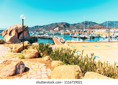 Boats in Beautiful Marina of Villasimius and the Bay of the Blue Waters of the Mediterranean Sea on Sardinia Island in Italy in summer. Cagliari region.
