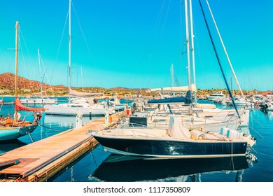 Boats at Beautiful Port of Villasimius in the Bay of the Blue Waters of the Mediterranean Sea on Sardinia Island in Italy in summer. Cagliari region.