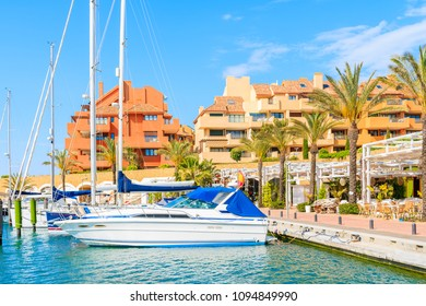 Boats in beautiful Sotogrande marina with colorful apartments and palm trees on shore, Costa del Sol, Spain