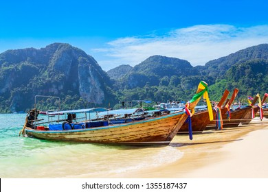 Boats at the beauty beach with limestone cliff and crystal clear water in Thailand