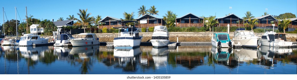 Boats berthed at a Tropical Marina with waterfront accommodation. Foreshore landscape and moored watercraft in smooth harbour water with reflections under a vibrant blue sky. Tin Can Bay, Queensland,