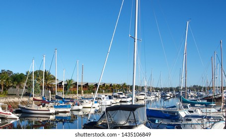 Boats berthed at a Tropical Marina. Waterfront foreshore landscape and moored watercraft in smooth harbour water with reflections under a vibrant blue sky. Tin Can Bay, Queensland, Australia.