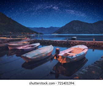 Boats in a Boka-Kotor bay under the night starry sky. Adriatic sea, Montenegro, Europe.