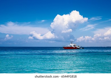 Boats in the Caribbean. A saturated blue sky, clouds and the sea.