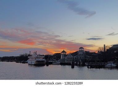 Boats, city skyline and waterfront of Alexandria, Virginia viewed from the water at sunset