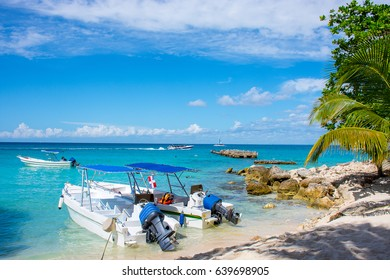 Boats in the clear ocean on a background of palm trees and beautiful clouds.
