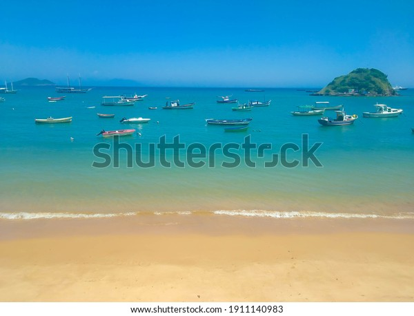 boats in the crystal blue-green sea on the beach in downtown Búzios, Rio de Janeiro