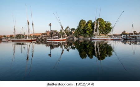 Boats at dawn moored on the banks reflected in the Nile at Aswan with the Sahara in the background and some trees.