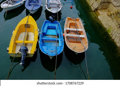 Boats of different colors tied up in the port
