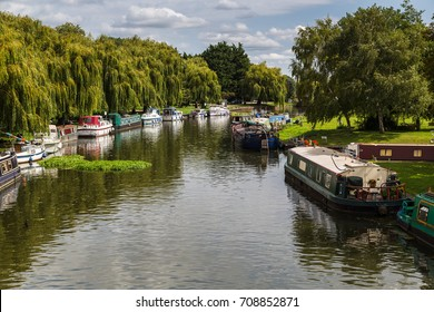 Boats of differing types and sizes line the banks of the River Great Ouse in Ely during the summer.