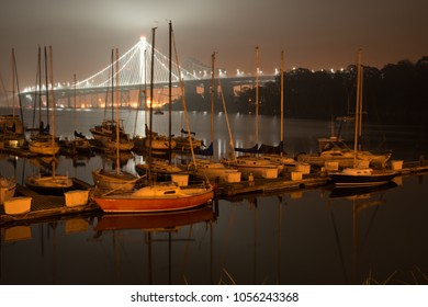 Boats at dock with the Bay Bridge in background at night, San Francisco, North Beach, California, USA