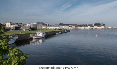 Boats docked at the Claddagh with  The Long Walk, Galway City in the background