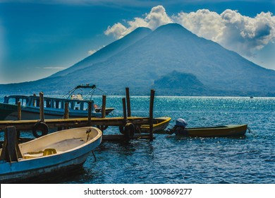 Boats docked in Lake Atitlán, Guatemala with volcanoes in the background.