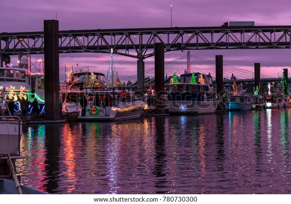 Boats Docked at Marina Adorned with Christmas Holiday Lights and Reflection in the Water.