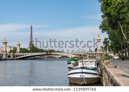Boats Docked on the Seine River, Pont Alexander III Bridge and the Eiffel Tower in Paris France.