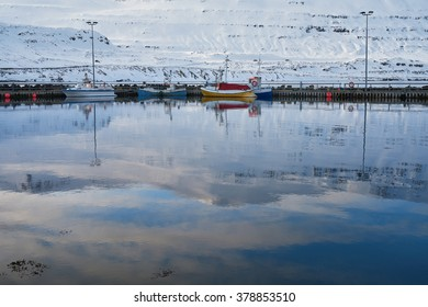 Boats docked at the quay pier in a small icelandic village, Seydisfjordur, calm water with reflection of vessels