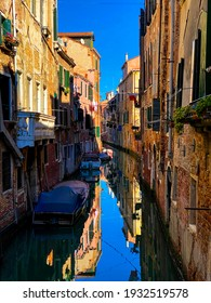Boats docking, laundry, balcony with plant in a small old colorful street in Venice, Italy