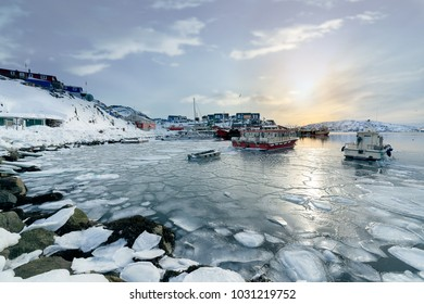 Boats are floating in the sea. The ice is frozen. Cover the surface of the sea. In the bay near the town center.qaqortoq greenland