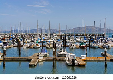 Boats in Gashouse Cove marina on San Francisco bay. Sailboats and yachts docked at wooden pier. View of hills in background.