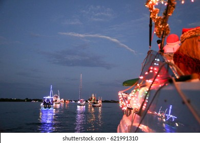 Boats with holiday lights on the water in Christmas boat parade
