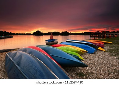 Boats and kayaks parked at the lakeside with beautiful sunset on the background in Putrajaya, Malaysia