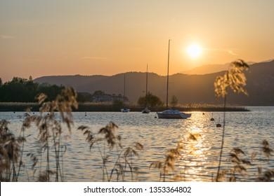 Boats at lake woerthersee during a beautiful orange sunset in autumn. Austria, carinthia, klagenfurt, wörthersee