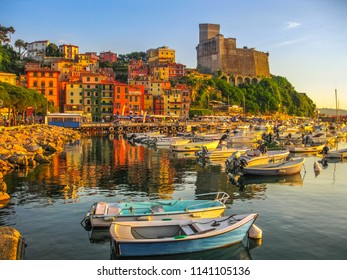Boats of Lerici docked in Lerici port and famous Italian Gulf of Poets. San Giorgio castle on the background at sunset. La Spezia province, Ligurian Coast of Italy.