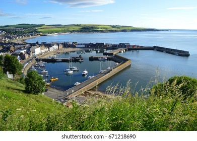 The boats lie still on a calm early summer's morning in Stonehaven harbour Scotland.