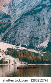 Boat's line on the mountain lake in front of autumn yellow forest and a gigantic rocks. Lago di Braies, Italy. Peaceful landscape